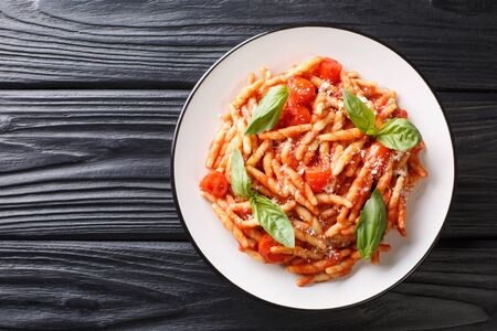 Pasta trofie recipe with tomato sauce, parmesan and basil close-up in a plate on the table. Horizontal top view from above