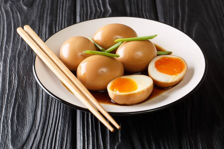Delicious soft-boiled Japanese eggs nitamago in soya marinade with green onions close-up in a plate on the table. horizontal  Zdjęcie Seryjne