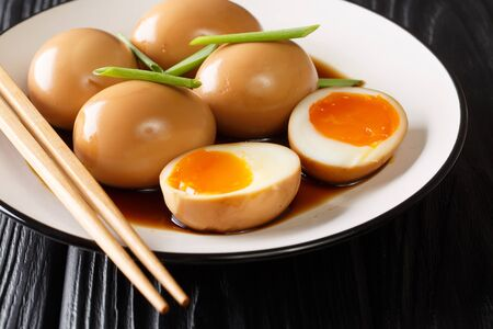 Soft-boiled eggs of nitamago in soya marinade with green onions close-up in a plate on the table. horizontal