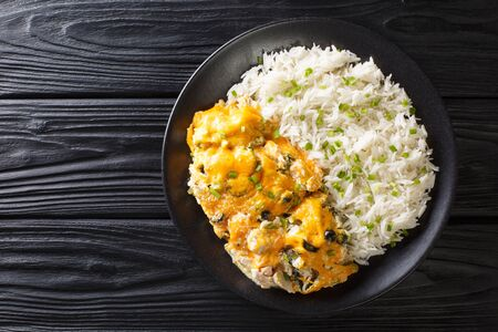 Homemade chicken casserole with olives, chili peppers and onions in a creamy cheese sauce served with rice close-up on a plate on the table. horizontal top view from above  Zdjęcie Seryjne