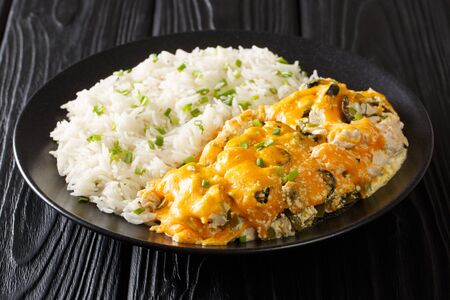 Serving Olivia chicken casserole with olives, chili peppers and onions in a creamy cheese sauce served with rice close-up on a plate on the table. horizontal  Zdjęcie Seryjne