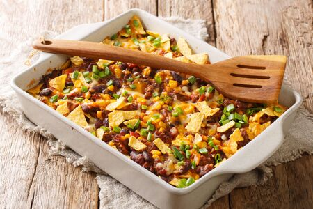 Crispy homemade frito pie with beef, cheese, corn, beans and chips close-up in a baking dish on the table. horizontal Reklamní fotografie