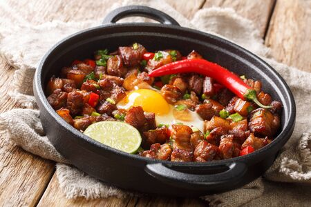 Sizzling spicy pork sisig with egg ang lime close-up in a pan on the table. Horizontal Banco de Imagens
