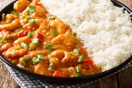 Louisiana shrimp Etouffee with vegetables cooked in roux sauce served with rice closeup in a plate on the table. horizontal