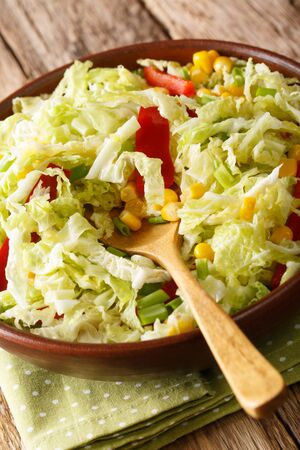 Savoy cabbage salad with corn, onions and bell pepper close-up in a bowl on the table. vertical