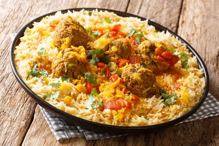 Afghan meat balls in spicy sauce with yellow peas served with basmati rice close-up in a plate on the table. horizontal