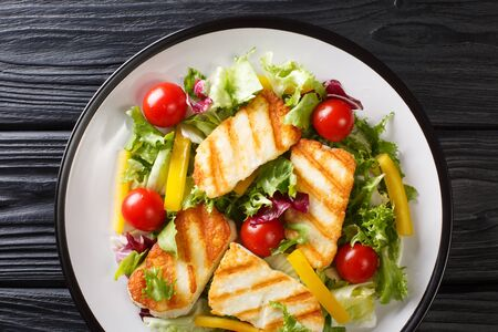 Tasty snack salad Grilled halloumi cheese filed with fresh vegetables close-up on the plate on the table. Horizontal v