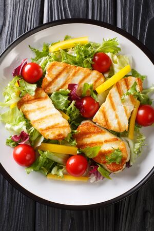 Fresh salad with grilled halloumi cheese with vegetables closeup at the plate on the table. Vertical top view from above  Stock Photo