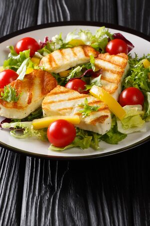 Cypriot salad of grilled halloumi cheese, tomatoes, peppers and lettuce closeup in a plate on the table. vertical  Stock Photo