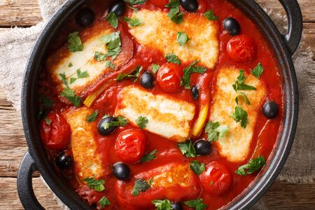 Cyprus food baked Halloumi with tomatoes, peppers, olives in a spicy sauce close-up in a pan on the table. Horizontal top view from above