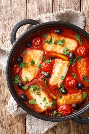 Baked Halloumi cheese with tomatoes, peppers, olives close-up in a pan on the table. Vertical top view from above  Stock Photo