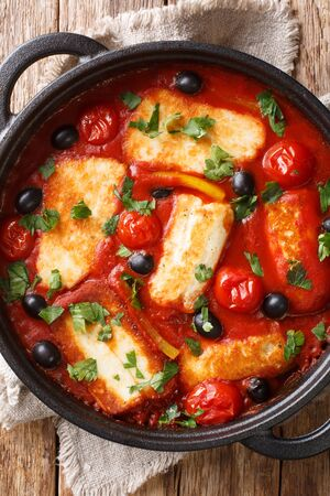 Tasty baked Halloumi with vegetables in tomato sauce close-up in a pan on the table. Vertical top view from above