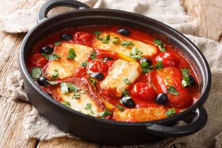 Traditional Halloumi cheese with tomatoes, peppers, olives in a spicy sauce close-up in a pan on the table. horizontal