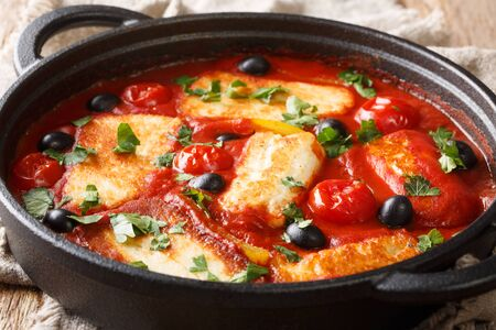 Cyprus food baked Halloumi with tomatoes, peppers, olives in a spicy sauce close-up in a pan on the table. horizontal