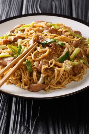 Traditional Chinese Shanghai noodles with napa cabbage, green onions and pork closeup in a plate on the table. vertical
