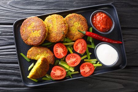 Yellow split pea fritters with fresh vegetables and sauces close-up in a plate on the table. Horizontal top view from above
