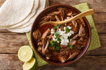 Birria is a Mexican dish is a spicy stew, traditionally made from goat meat closeup in a bowl on the table. Horizontal top view from above
