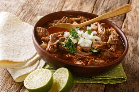 Serving of hot Birria de Res served with lime and tortilla closeup in a bowl on the table. horizontal