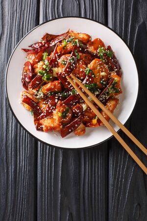 Mala Chicken Spicy Sichuan Chicken with dry chili pepper, sesame seeds and herbs close-up in a plate on the table. Vertical top view from above