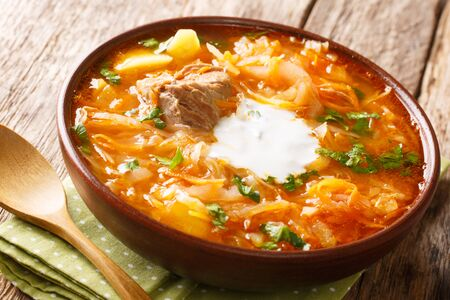 Traditional soup of Russia Shchi with beef served with sour cream close-up in a bowl on the table. Stock Photo