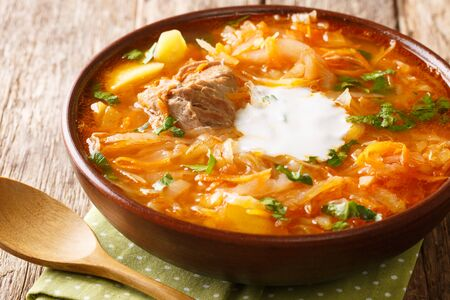 Russian sour cabbage soup shchi with beef in a clay bowl on a wooden background.