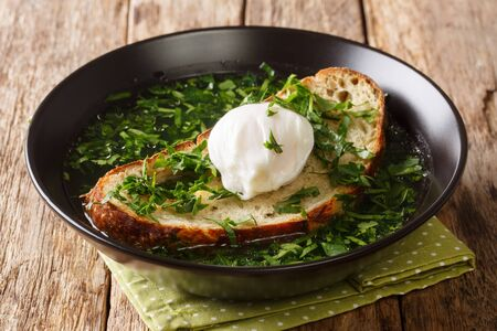 Summer Acorda Soup with cilantro, garlic, homemade bread and poached egg close-up in a bowl on the table. horizontal