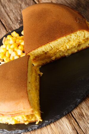 Apam Balik stuffed with sweet corn, peanuts, butter and sugar close-up on the table. vertical 版權商用圖片