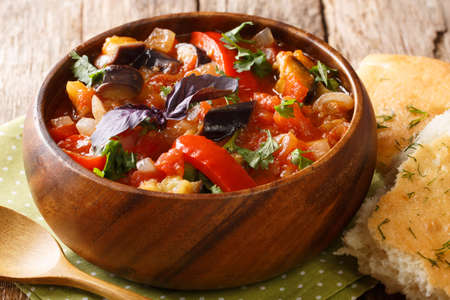 Summer spicy appetizer of eggplant, onions, tomatoes and sweet pepper close-up in a bowl on the table. horizontal