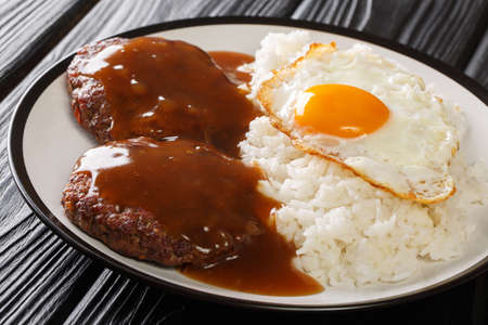 classic Hawaiian dish, Loco Moco consists of steamed rice with juicy hamburger steak, fried egg and smothered in a flavorful gravy close-up on a plate on the table. Horizontal top view from above Stock Photo