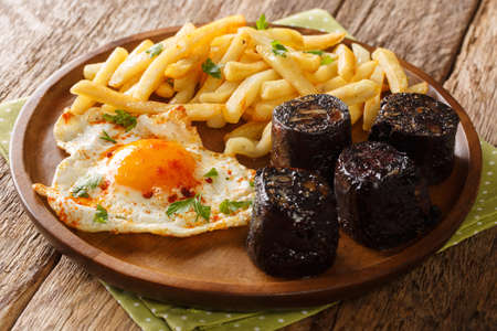 Huevos Rotos with fried potatoes and black pudding close-up in a plate on the table. Horizontal