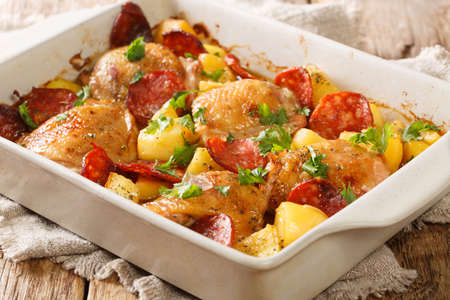 Traditional spanish food chicken with new potatoes and chorizo sausage close-up in a baking dish on the table. horizontal