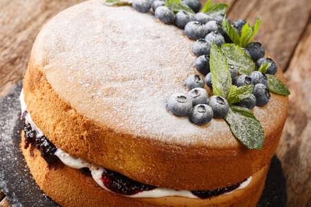 Victoria sponge cake recipe combines blueberry jam and cream closeup on the slate board on the table. Horizontal Stock Photo