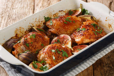 Honey chicken thighs baked with ripe figs, mustard and herbs close-up in a baking dish on the table. horizontal
