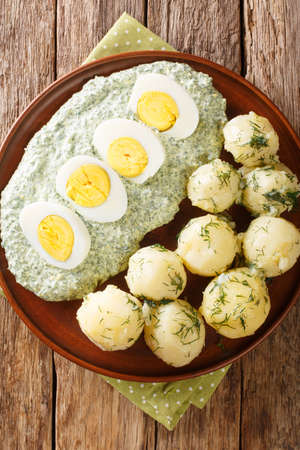 German cuisine boiled potatoes with eggs frankfurt green sauce close-up in a plate. Vertical top view from above 免版税图像