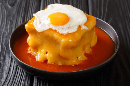 Portuguese delicious Francesinha sandwich with meat sausages, melted cheese, drizzled with tomato beer sauce and topped with a fried egg close-up in a plate on the table. horizontal