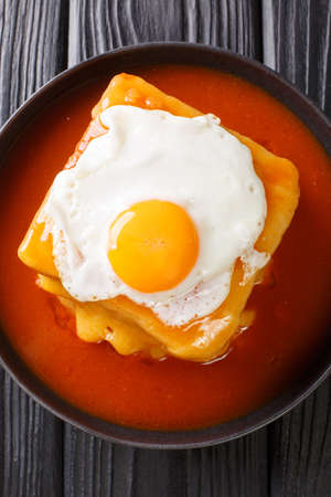 Francesinha is a unique sandwich consisting of toasted bread, beef, sausages, ham, and cheese, doused in a rich beer infused tomato sauce close-up in a plate. Vertical top view from above 免版税图像
