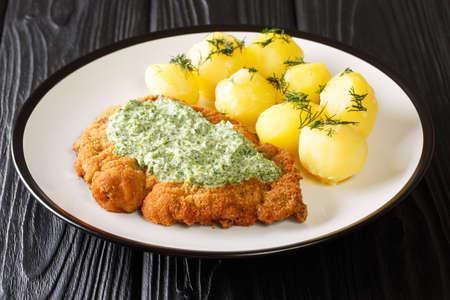 Portion of fried breaded schnitzel with boiled potatoes and Frankfurt green sauce close-up in a plate on the table. horizontal