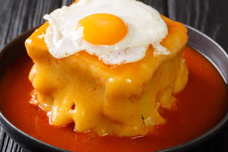 Delicious big Portuguese hot sandwich Francesinha with different types of sausages and meat, poured with cheese with tomato beer sauce and topped with a fried egg 免版税图像