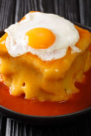 Francesinha is a Portuguese hot sandwich made of bread, beef, sausages, ham and cheese, drenched in tomato sauce with beer and topped with a fried egg Stock fotó - 155444902