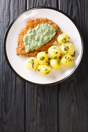 Traditional Frankfurt cuisine schnitzel with boiled new potatoes and green sauce close-up in a plate on the table. Vertical top view from above