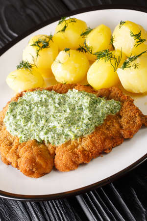 German schnitzel with boiled potatoes and Frankfurt green sauce close-up in a plate on the table. vertical 免版税图像