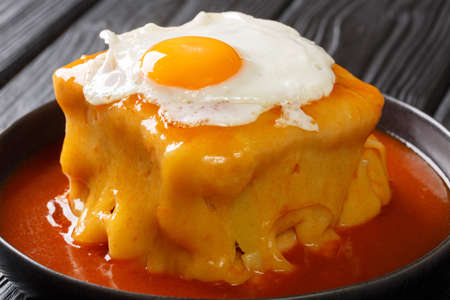 Francesinha is a Portuguese sandwich originally from Porto, made with bread, ham, linguica, sausage, steak, and covered with melted cheese and a hot and thick spiced tomato and beer sauce Imagens