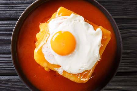 Francesinha Portuguese croque madame sandwich close-up in a plate on the table. Horizontal top view from above