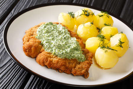 Delicious German food schnitzel with boiled new potatoes and the famous Frankfurt green sauce close-up in a plate on the table. horizontal