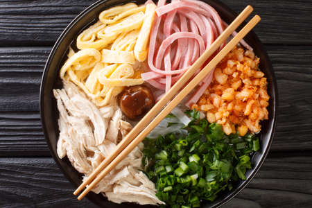 Hanoi Noodle Soup with Ham Chicken and Shrimp Bun Thang closeup in the plate on the table. Horizontal top view from above 免版税图像