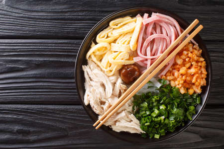 Hanoi noodle soup with chicken, ham, shrimps, egg and herbs close-up in a bowl on the table. horizontal top view from above
