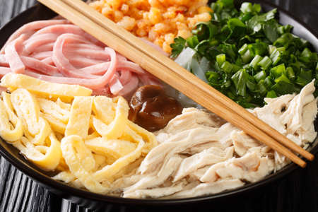 Vietnamese hot noodle soup with chicken, ham, shrimps, egg and herbs close-up in a bowl on the table. horizontal 免版税图像