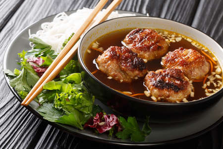 Bun cha is a delicious balance of noodles, a lot of herbs, a beautiful dressing and meatballs cooked over fire closeup in the plate on the table. Horizontal