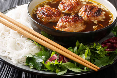 Bun cha is a Vietnamese dish of grilled pork, noodle and herb closeup in the plate on the table. Horizontal