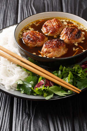 Bun cha consists of rice vermicelli noodles (bun), grilled pork (cha) and a type of broth closeup in the plate on the table. Vertical 免版税图像